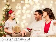 Купить «happy family with christmas present at home», фото № 32144754, снято 11 января 2018 г. (c) Syda Productions / Фотобанк Лори