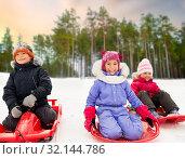 Купить «happy little kids sliding down on sleds in winter», фото № 32144786, снято 10 февраля 2018 г. (c) Syda Productions / Фотобанк Лори