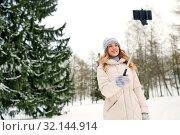 Купить «woman taking picture by selfie stick in winter», фото № 32144914, снято 20 января 2019 г. (c) Syda Productions / Фотобанк Лори