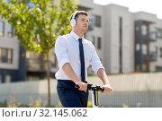 Купить «businessman with headphones riding scooter in city», фото № 32145062, снято 1 августа 2019 г. (c) Syda Productions / Фотобанк Лори
