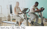 Купить «African man and Caucasian woman exercising on stationary bikes at gym», видеоролик № 32145742, снято 24 марта 2019 г. (c) Яков Филимонов / Фотобанк Лори