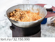 Купить «Cooking pilaf with meat in a large cauldron», фото № 32150990, снято 10 марта 2019 г. (c) FotograFF / Фотобанк Лори