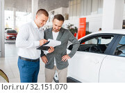 Salesman and buyer make out the purchase of car. Стоковое фото, фотограф Tryapitsyn Sergiy / Фотобанк Лори