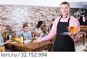Energetic waiter showing hospitality and meeting visitors in cafe. Стоковое фото, фотограф Яков Филимонов / Фотобанк Лори