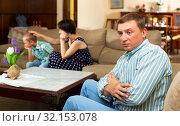 Unhappy man sitting at sofa after family quarrelling, woman with son. Стоковое фото, фотограф Яков Филимонов / Фотобанк Лори