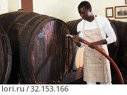 Купить «man winegrower works in a wine-vault», фото № 32153166, снято 1 августа 2019 г. (c) Яков Филимонов / Фотобанк Лори