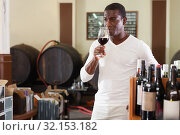 Купить «Confident african american male winemaker inspecting quality of red wine, checking it in wine store», фото № 32153182, снято 1 августа 2019 г. (c) Яков Филимонов / Фотобанк Лори