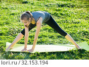 Купить «sporty female doing aerobics on mat in green park», фото № 32153194, снято 8 июня 2017 г. (c) Яков Филимонов / Фотобанк Лори
