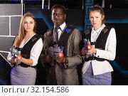 Купить «African man and two women at laser tag room», фото № 32154586, снято 4 апреля 2019 г. (c) Яков Филимонов / Фотобанк Лори