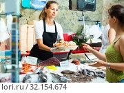Купить «Nice woman demonstrating raw prawns», фото № 32154674, снято 21 мая 2020 г. (c) Яков Филимонов / Фотобанк Лори