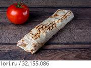 Купить «Шаурма и красный томат на деревянном фоне», фото № 32155086, снято 26 февраля 2020 г. (c) Sergei Gorin / Фотобанк Лори