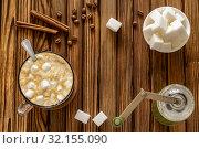 Кофе с молоком и маршмеллоу, ручная кофемолка, сахар  и палочки корицы. Стоковое фото, фотограф Sergei Gorin / Фотобанк Лори