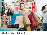Two girls holding a paper shopping bags in the boutique. Стоковое фото, фотограф Яков Филимонов / Фотобанк Лори
