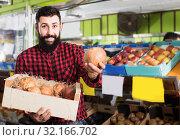 Купить «Male seller showing pomegranates in grocery store», фото № 32166702, снято 15 ноября 2016 г. (c) Яков Филимонов / Фотобанк Лори
