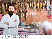 Купить «Man seller showing sorts of meat in butcher's shop», фото № 32166710, снято 16 ноября 2016 г. (c) Яков Филимонов / Фотобанк Лори