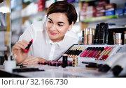 Купить «Female customer searching for reliable make-up products», фото № 32166730, снято 31 января 2017 г. (c) Яков Филимонов / Фотобанк Лори