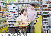 Купить «Woman with girl looking for food in supermarket», фото № 32166738, снято 5 января 2017 г. (c) Яков Филимонов / Фотобанк Лори