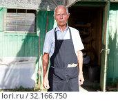 Купить «Serious gardener near garden shed», фото № 32166750, снято 13 июня 2018 г. (c) Яков Филимонов / Фотобанк Лори