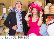 Купить «Happy woman and man trying on fashion hats», фото № 32166950, снято 2 мая 2017 г. (c) Яков Филимонов / Фотобанк Лори