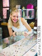 Купить «woman seller showing bracelets», фото № 32166998, снято 20 октября 2019 г. (c) Яков Филимонов / Фотобанк Лори