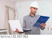 Купить «Constructor is standing with laptop and folder with documents», фото № 32167362, снято 18 мая 2017 г. (c) Яков Филимонов / Фотобанк Лори