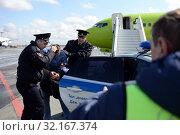 Полицейские выводят авиационного дебошира с борта самолёта (2018 год). Редакционное фото, фотограф Free Wind / Фотобанк Лори