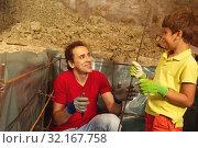 Купить «Boy give father metal rod bar to make basement», фото № 32167758, снято 10 июня 2018 г. (c) Сергей Новиков / Фотобанк Лори