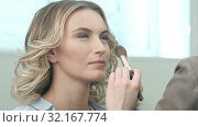 Купить «Applying blush makeup with brush to cheekbones of smiling young woman», видеоролик № 32167774, снято 14 апреля 2017 г. (c) Vasily Alexandrovich Gronskiy / Фотобанк Лори