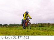 Купить «Bikepacker looks at the road while riding across the field in the rain», фото № 32171162, снято 3 сентября 2019 г. (c) Евгений Харитонов / Фотобанк Лори