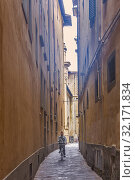 A lone cyclist on the Via de Giacomini in the back streets of Florence, Centro Storico, Firenze, Tuscany, Italy. Редакционное фото, фотограф Cahir Davitt / age Fotostock / Фотобанк Лори