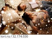 Купить «happy couple with garland lying on floor at home», фото № 32174030, снято 13 января 2018 г. (c) Syda Productions / Фотобанк Лори