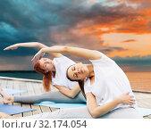 Купить «women making yoga exercises outdoors», фото № 32174054, снято 7 августа 2016 г. (c) Syda Productions / Фотобанк Лори
