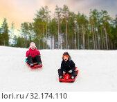 Купить «happy kids sliding on sleds down hill in winter», фото № 32174110, снято 10 февраля 2018 г. (c) Syda Productions / Фотобанк Лори