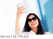 Купить «asian woman taking selfie by smartphone in city», фото № 32174222, снято 13 июля 2019 г. (c) Syda Productions / Фотобанк Лори