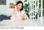 Купить «asian woman with smartphone and earphones at cafe», фото № 32174226, снято 13 июля 2019 г. (c) Syda Productions / Фотобанк Лори
