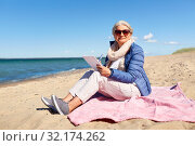 Купить «senior woman writing to notebook on summer beach», фото № 32174262, снято 28 июня 2019 г. (c) Syda Productions / Фотобанк Лори