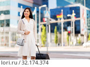 Купить «happy young asian woman with travel bag in city», фото № 32174374, снято 13 июля 2019 г. (c) Syda Productions / Фотобанк Лори