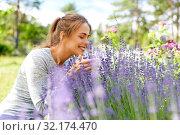 Купить «young woman smelling lavender flowers in garden», фото № 32174470, снято 12 июля 2019 г. (c) Syda Productions / Фотобанк Лори