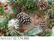Купить «Christmas or New Year festive decorative natural background with a wooden texture with snowy green and white branches of spruce with cones and red berries», фото № 32174886, снято 11 сентября 2019 г. (c) Светлана Евграфова / Фотобанк Лори
