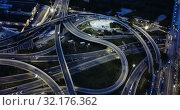 Купить «Aerial view of modern city highway grade separation in night lights», видеоролик № 32176362, снято 26 октября 2018 г. (c) Яков Филимонов / Фотобанк Лори