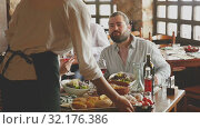 Купить «Happy people having dinner at rural restaurant and drinking wine», видеоролик № 32176386, снято 26 апреля 2019 г. (c) Яков Филимонов / Фотобанк Лори