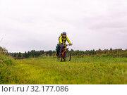 Купить «Cyclist traveler rides through an autumn meadow on a cloudy day», фото № 32177086, снято 3 сентября 2019 г. (c) Евгений Харитонов / Фотобанк Лори