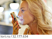 Woman holding smartphone makes voice message chat to friend distantly. Стоковое фото, фотограф Alexander Tihonovs / Фотобанк Лори