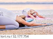 Купить «Group of women do Child pose Balasana exercise outdoors», фото № 32177754, снято 16 июня 2019 г. (c) Alexander Tihonovs / Фотобанк Лори