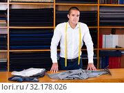 Купить «Confident salesman standing next to cutting table», фото № 32178026, снято 18 ноября 2019 г. (c) Яков Филимонов / Фотобанк Лори