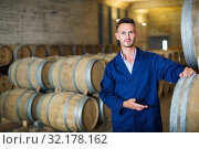 Man working on secondary fermentation equipment in winery manufactory. Стоковое фото, фотограф Яков Филимонов / Фотобанк Лори