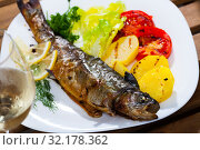 Купить «Roasted trout with potatoes, tomatoes and glass of white wine», фото № 32178362, снято 16 сентября 2019 г. (c) Яков Филимонов / Фотобанк Лори
