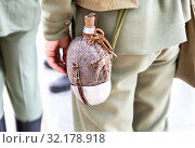 Vintage military flask hangs on a belt from a soldier. Стоковое фото, фотограф FotograFF / Фотобанк Лори