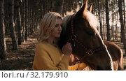 Young female horseback coach hugs the nice male brown horse with white mane with love slow motion. Стоковое видео, видеограф Denis Mishchenko / Фотобанк Лори