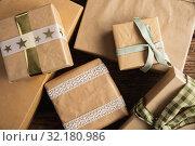 Купить «Simple wrapped gifts on wooden table», фото № 32180986, снято 13 августа 2019 г. (c) Wavebreak Media / Фотобанк Лори